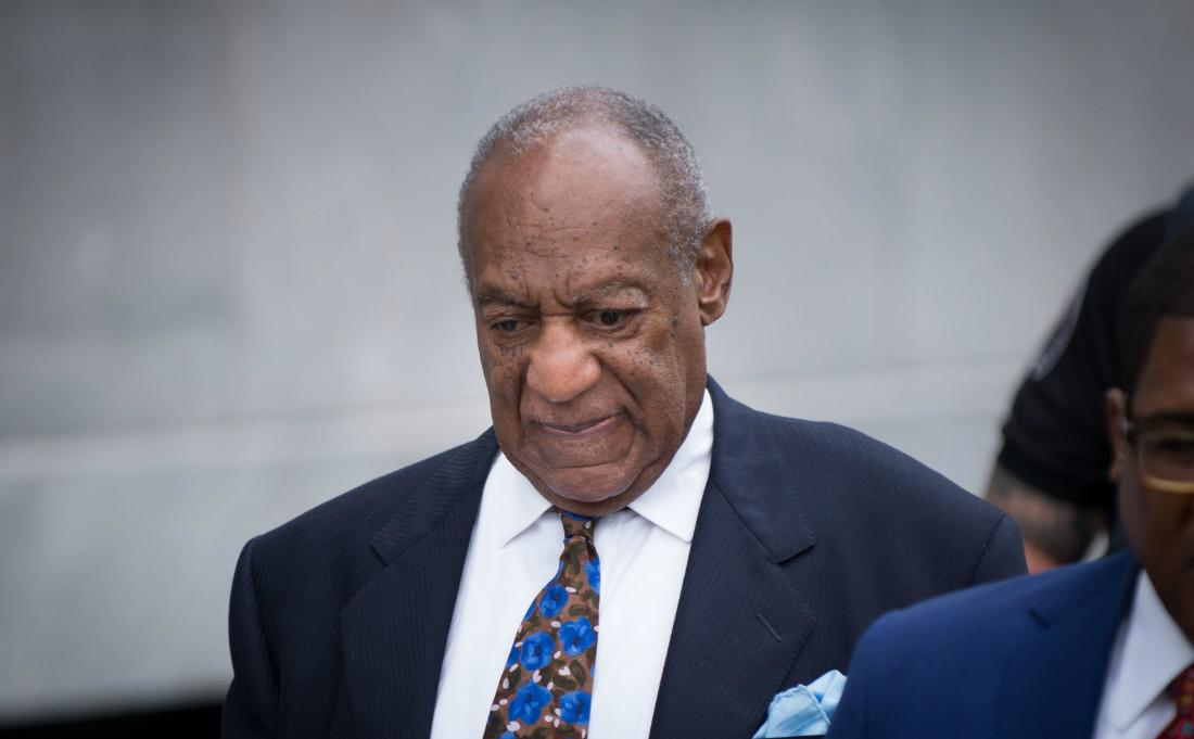 Bill Cosby wears a dark suit, white shirt, and patterned tie.