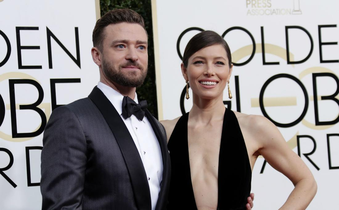 Justin Timberlake, in a black tux and white shirt, stands on the red carpet next to Jessica Biel who wears a black dress with a plunging neckline.