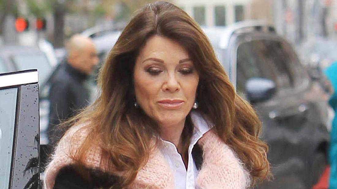 Lisa Vanderpump is seen wearing a pink scarf and a white shirt while looking down.