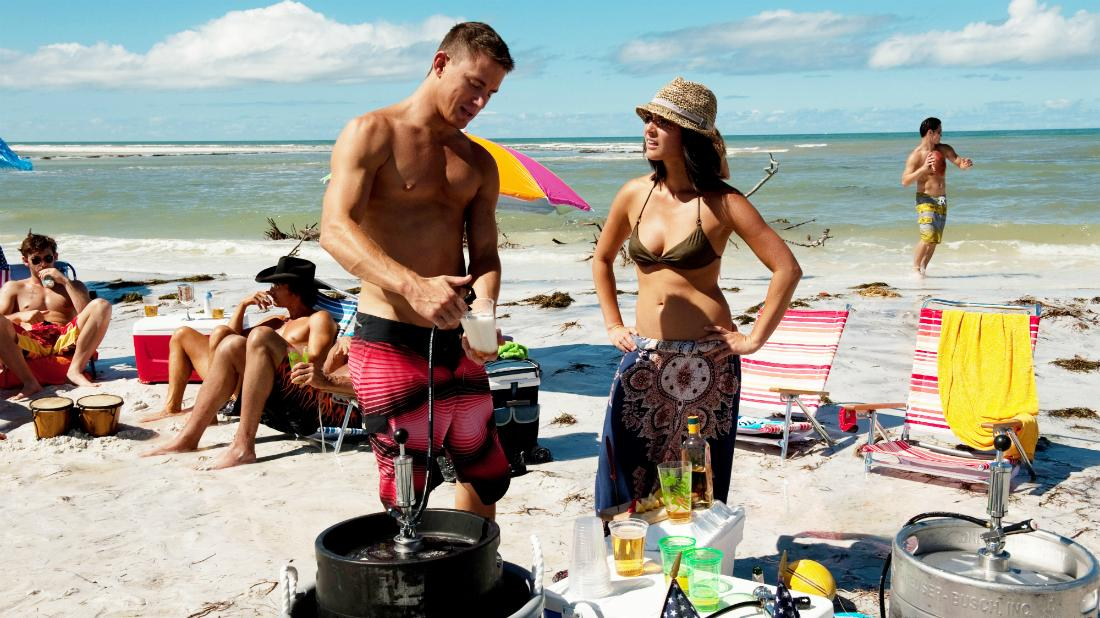Channing Tatum stood shirtless in a pair of red shorts alongside Olivia Munn who wore a deep green bikini top and colorful sarong.