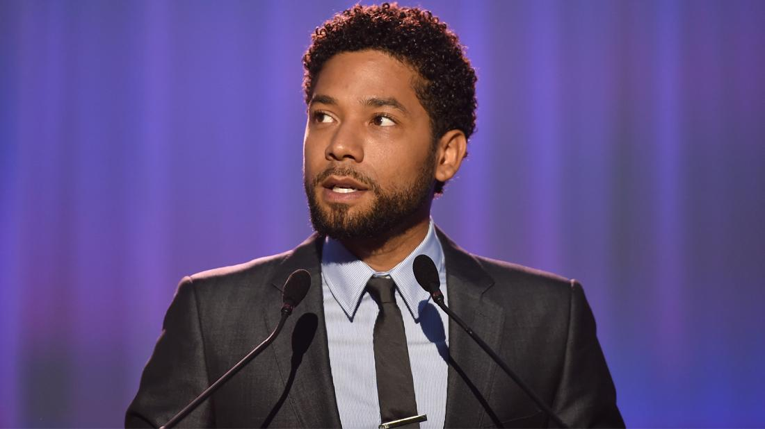 Jussie Smollet wears a gray shirt and black tie.