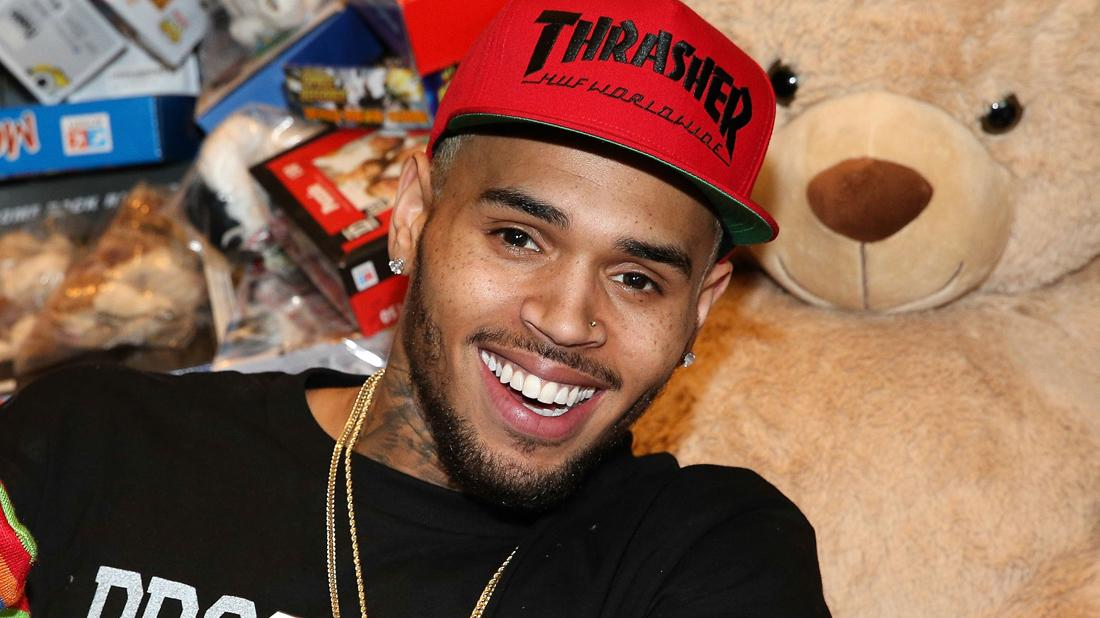 Chris Brown wears a black shirt with a red cap that says THRASHER on it.