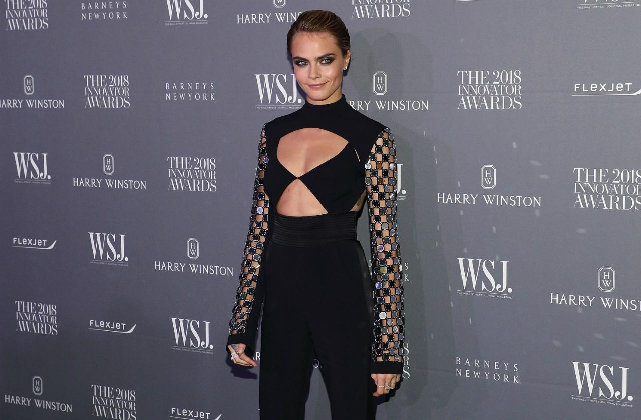 Cara Delevingne wears a black cleavage and stomach baring top and black pants, with her hair slicked back and a smoky eye makeup at the 2018 WSJ Magazine Innovator Awards.