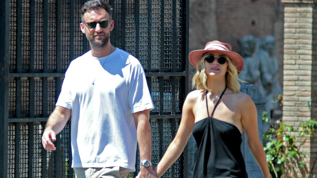 Jennifer Lawrence wore a black sundress and sun hat walking in Rome with her fiancé, Cooke Maroney, who was dressed in a T-shirt and casual slacks.