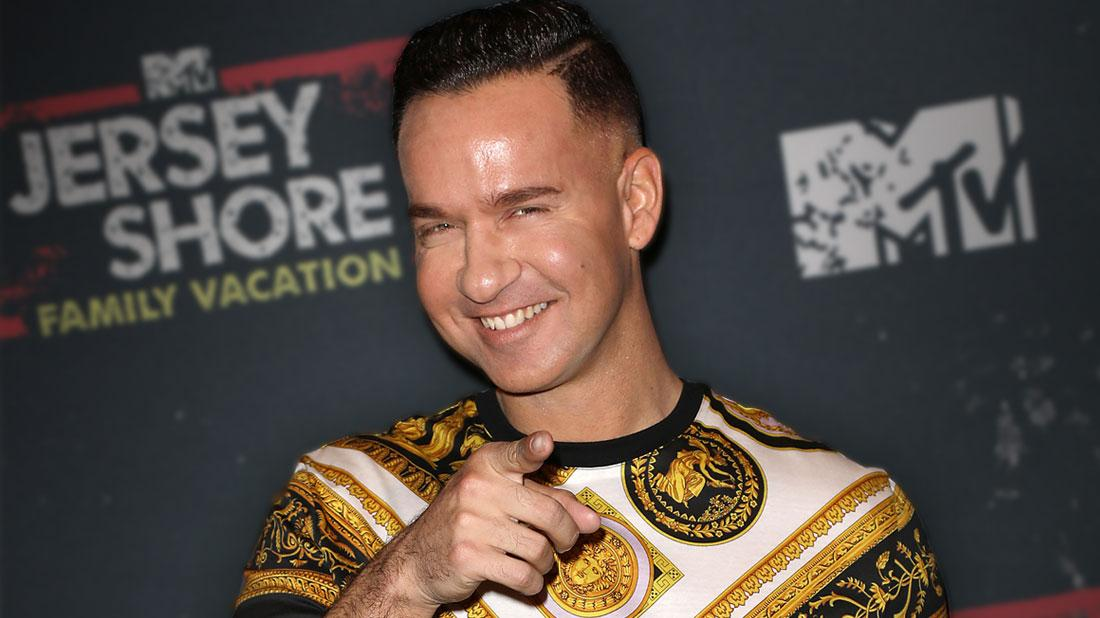 Smiling Mike Sorrentino Pointing At Camera Wearing A Black Gold And White Top