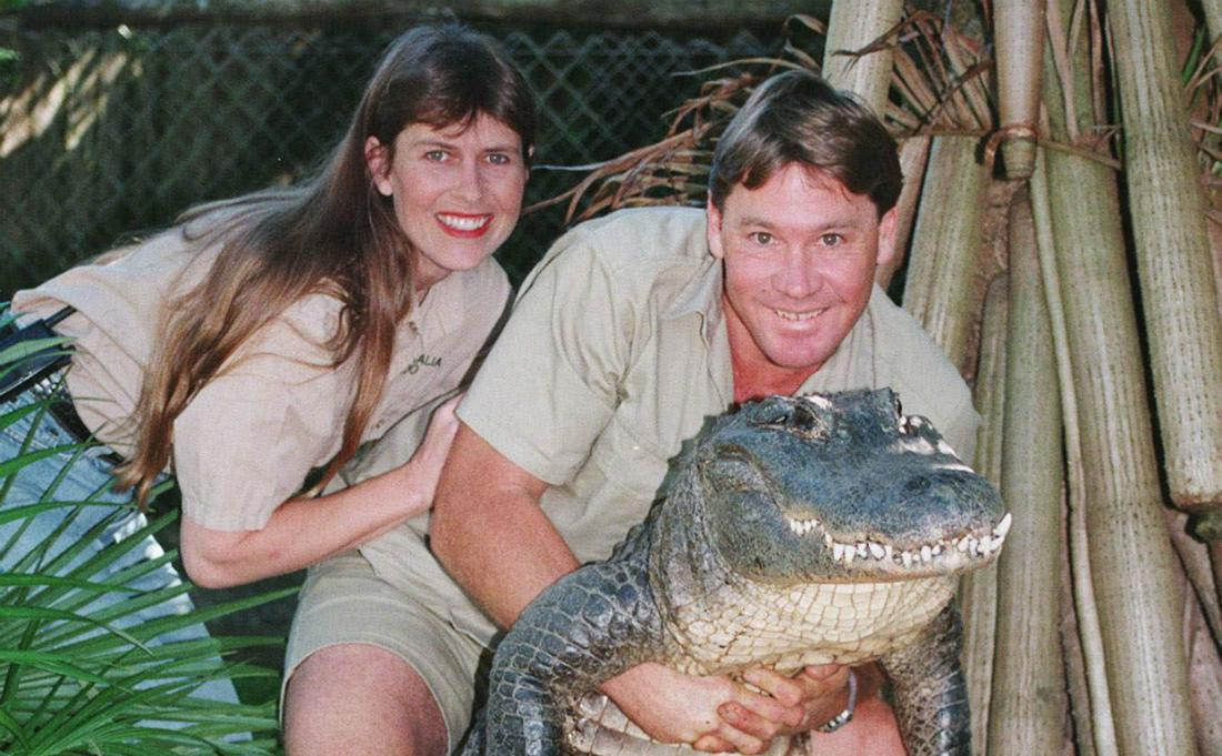 Dressed in khaki shorts and shirt, Steve Irwin smiles as he poses with an alligator. His wife, dressed in similar style, stands next to him, her hand on his arm.