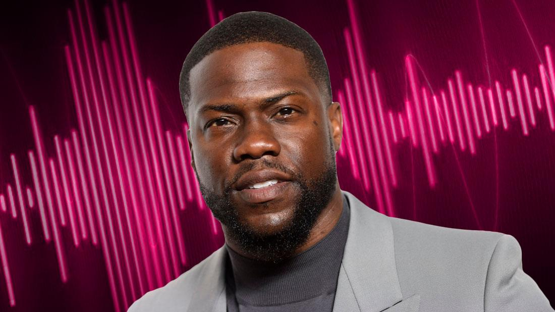 Closeup Of Kevin Hart Wearing Medium Gray Turtleneck and Light Gray Blazer WIth Pink Audio Waves in Background