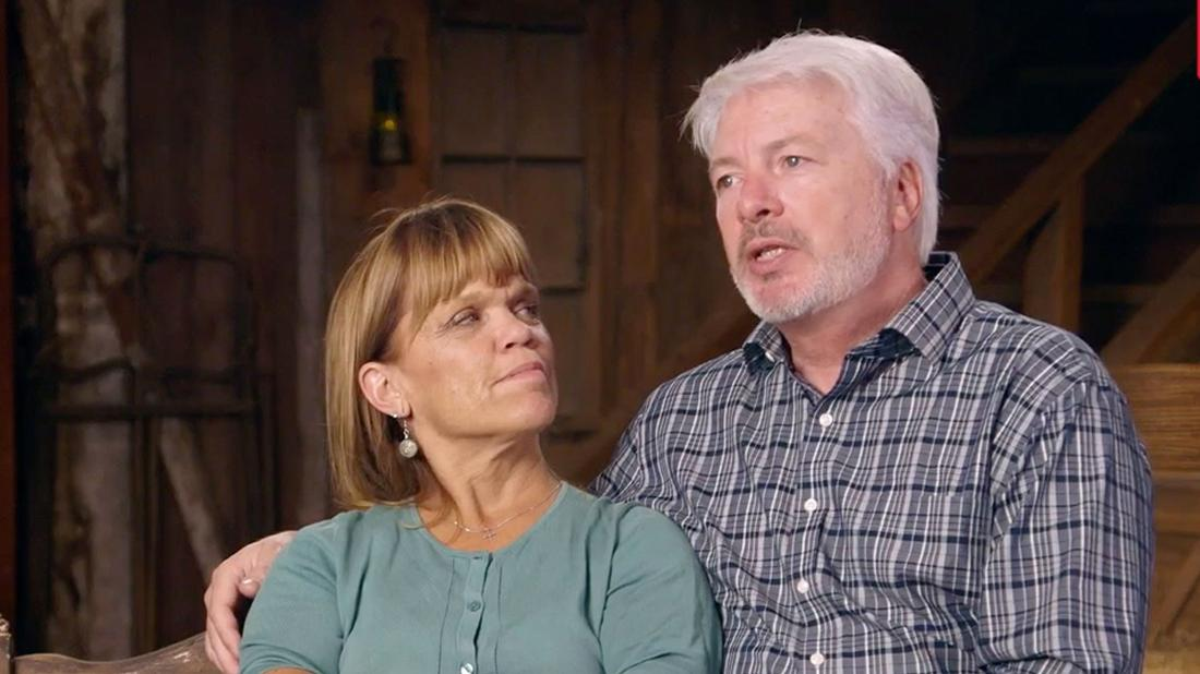 Amy Roloff Sitting Beside Chris Marek Looking Up At Him As They Both Have Serious Expressions