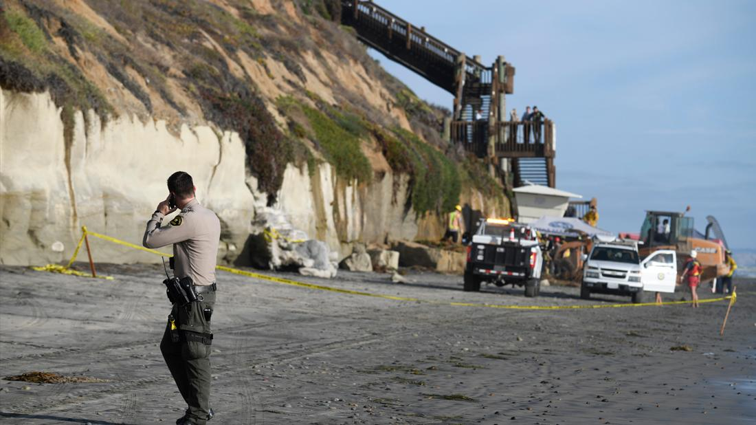 A San Diego County Sheriff's deputy looks on as search and rescue personnel work at the site of a cliff collapse at a popular beach, in Encinitas, Calif.