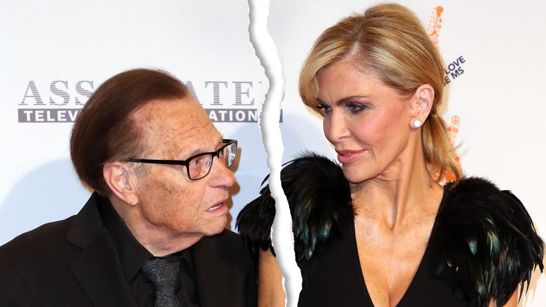 Larry King in Black Suit Holding Hands With Wife Shawn in Black Feather Dress As They Both look At Each Other Concerned With Rip Tear Graphic Through