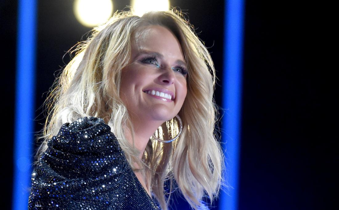Miranda Lambert smiles while on stage, wearing a sparkly black dress.