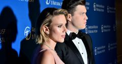 Colin Jost, in a black tux, stands next to Scarlett Johansson who wears a pink dress on the red carpet.