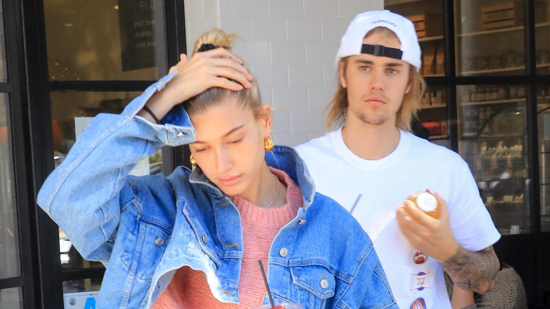 Justin Bieber wears a white shirt and a white cap. Hailey Baldwin is in front with a denim jacket and a pink sweater.