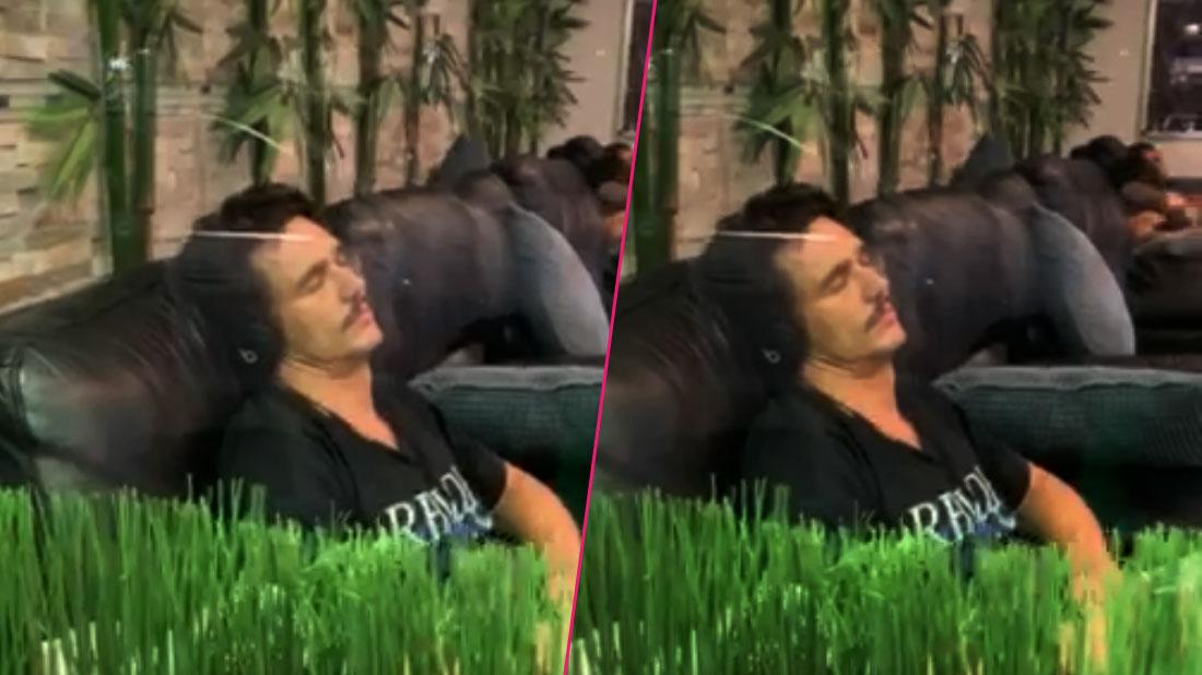 James Franco wears a black shirt while sleeping on the massage chair listening to music.