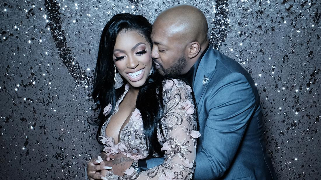 Dennis McKinley In Suit Holding a Pregnant Porsha Williams in Embellished Dress From Behind Kissing Her Cheek As She Smiles
