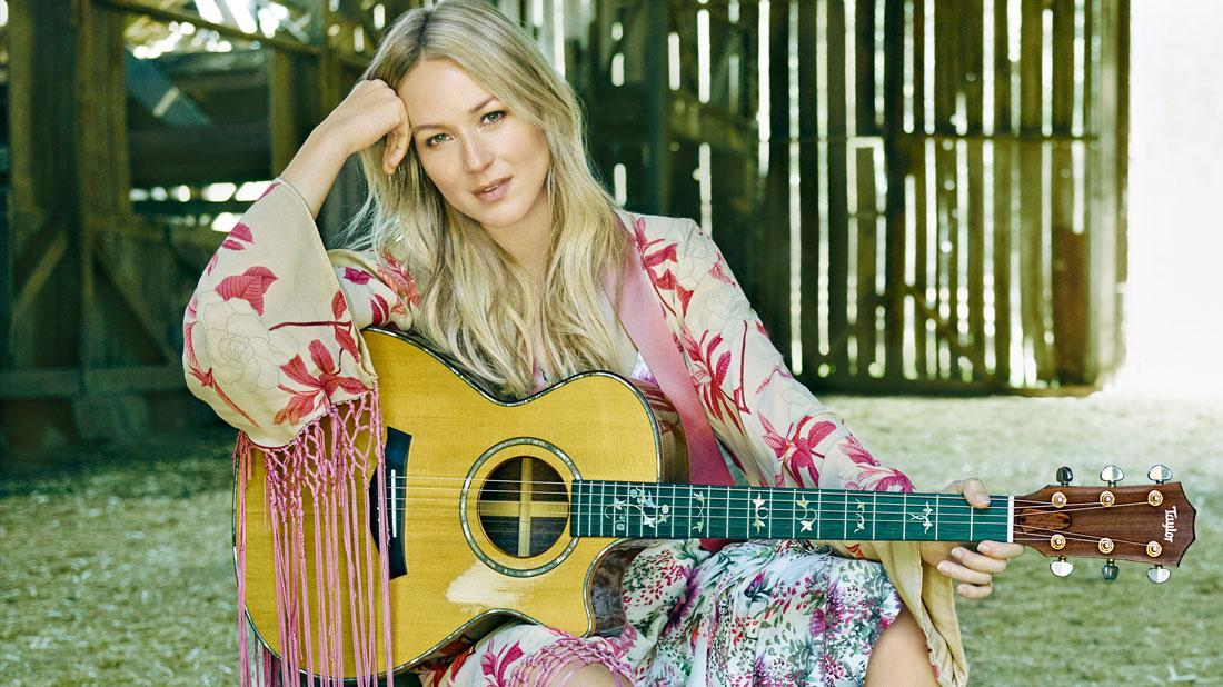Jewel Sitting with a Guitar on a Chair in a Barn