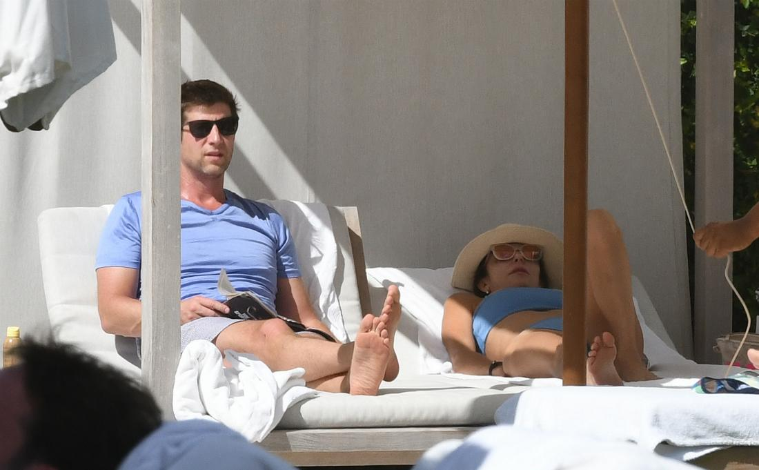 Paul Bernon, in a blue t-shirt, lays on a lounger next to Bethenny Frankel who wears a matching blue swimsuit.