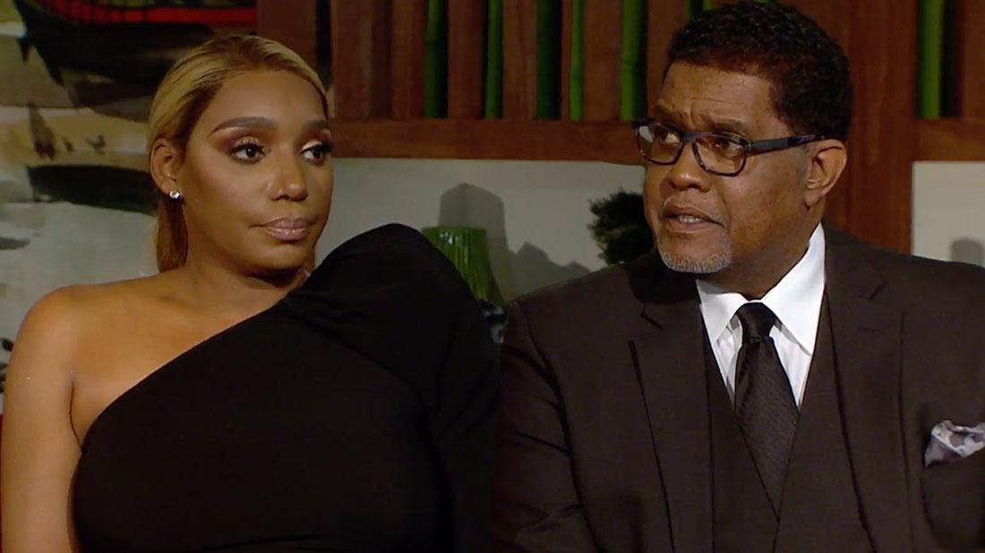 Nene Leakes Wearing One Shoulder Black Dress Sitting With Husband Greg Leakes Wearing A Brown Three Piece Siut White Shirt, Brown Tie