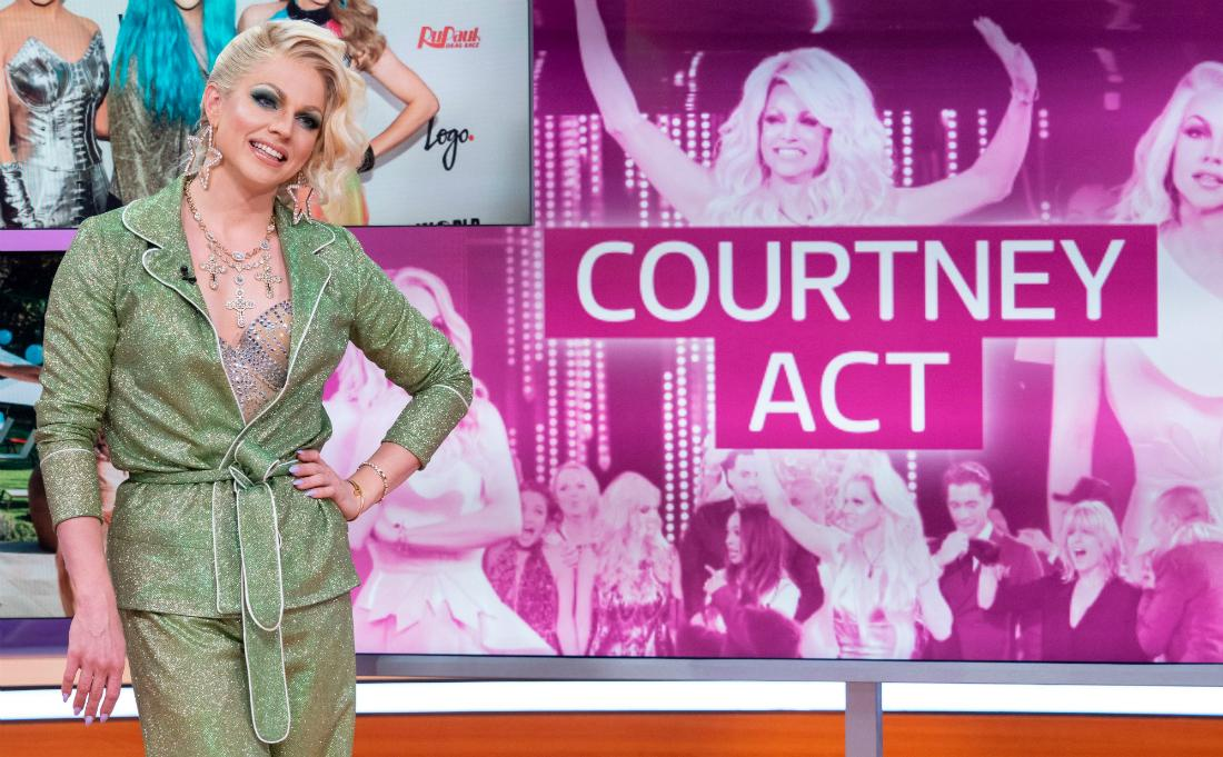 Courtney Act, in a glittery green pantsuit, stands on set with her name behind her.