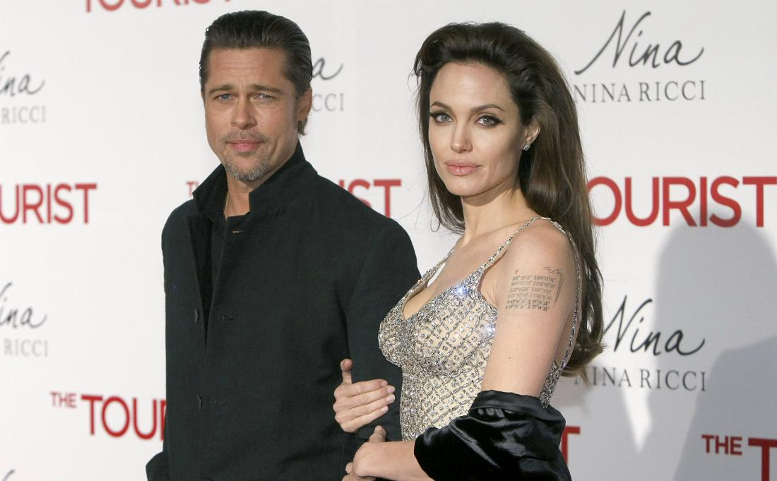 Brad Pitt, in black, poses on the red carpet with Angelina Jolie who wears a silvery top.