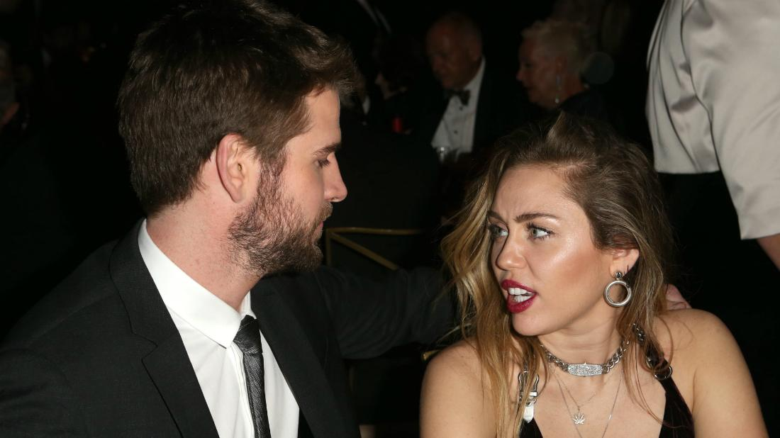 Liam Hemsworth, in a black suit, and Miley Cyrus, in a plunging black dress, during happier days before their divorce.
