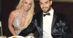 Britney Spears sits with her boyfriend at a table.