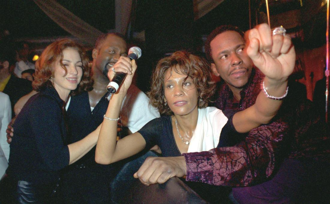 Whitney Houston, in black and clutching a mic, is flanked by Bobby Brown and Gloria Estefan.