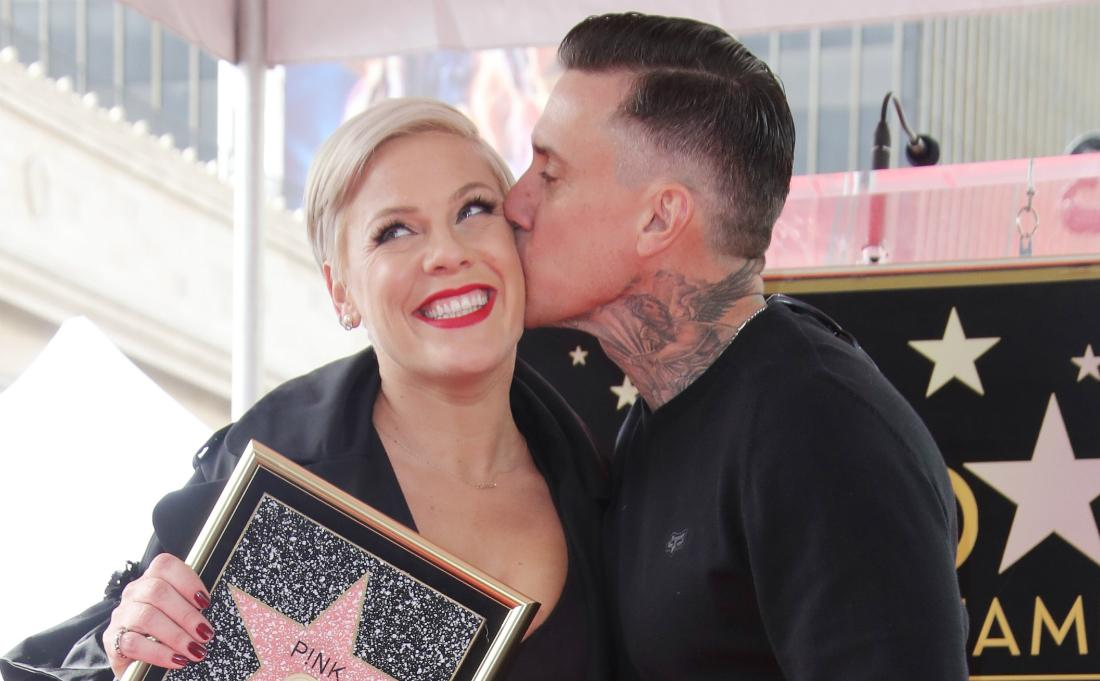 Pink, in a black and white dress, clutches a walk of fame picture and is being kissed by Carey Hart.