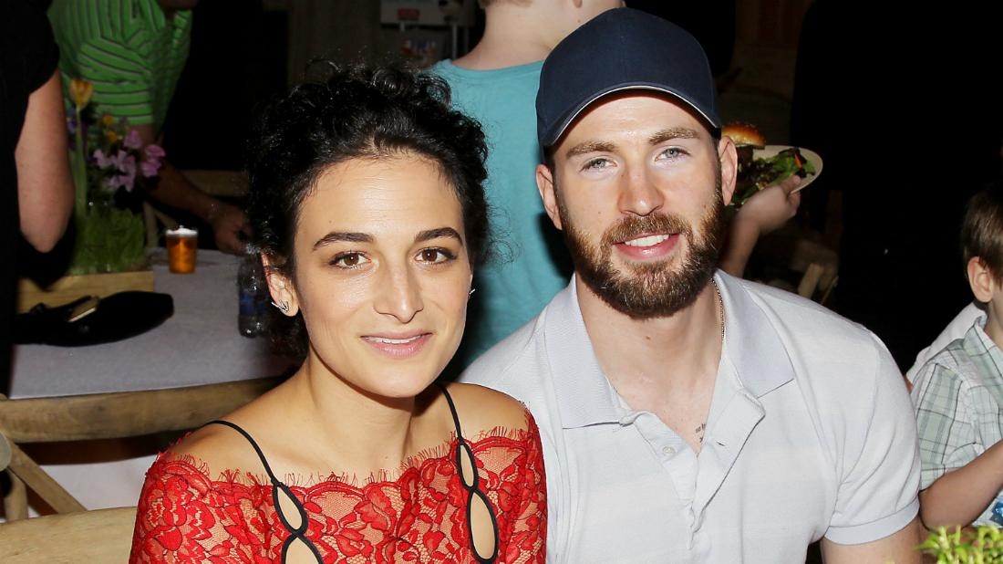 Jenny Slate wore a red dress with black spaghetti straps while Chris Evans donned a white Izod and a blue baseball hat.