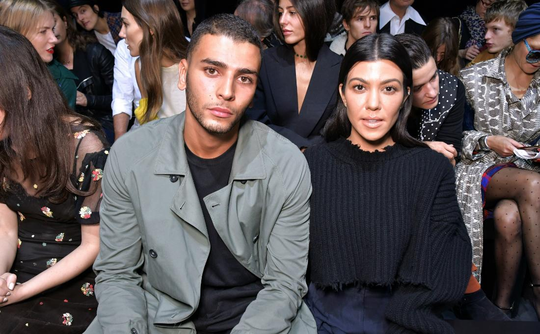 Kourtney Kardashian is all in black and sits next to Younes Bendjima who wears a grey jacket and black top.
