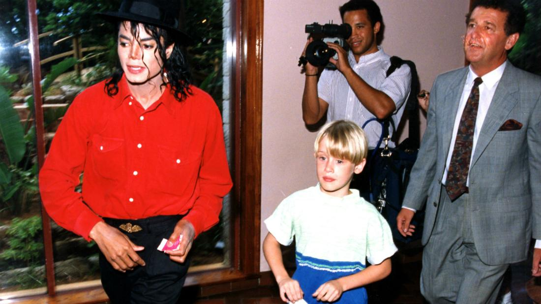 Michael Jackson in a red buttoned-down shirt with black pants posed with Macauley Culkin in a pair of shorts and a yellow and blue shirt.