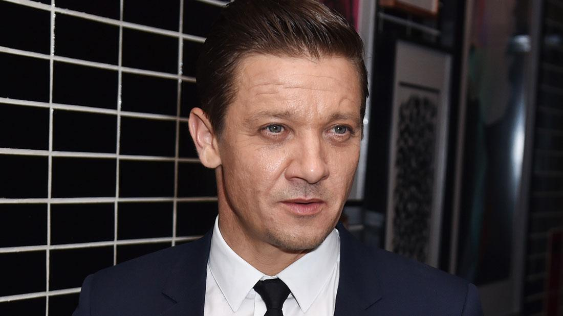 Jeremy Renner Wearing Black Tie and Dark Blue Suit With White Shirt