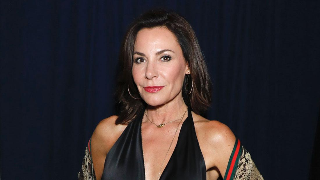 Luann de Lesseps Wearing Black Halter Jumopsuit With Gucci Scarf Around Her Arms