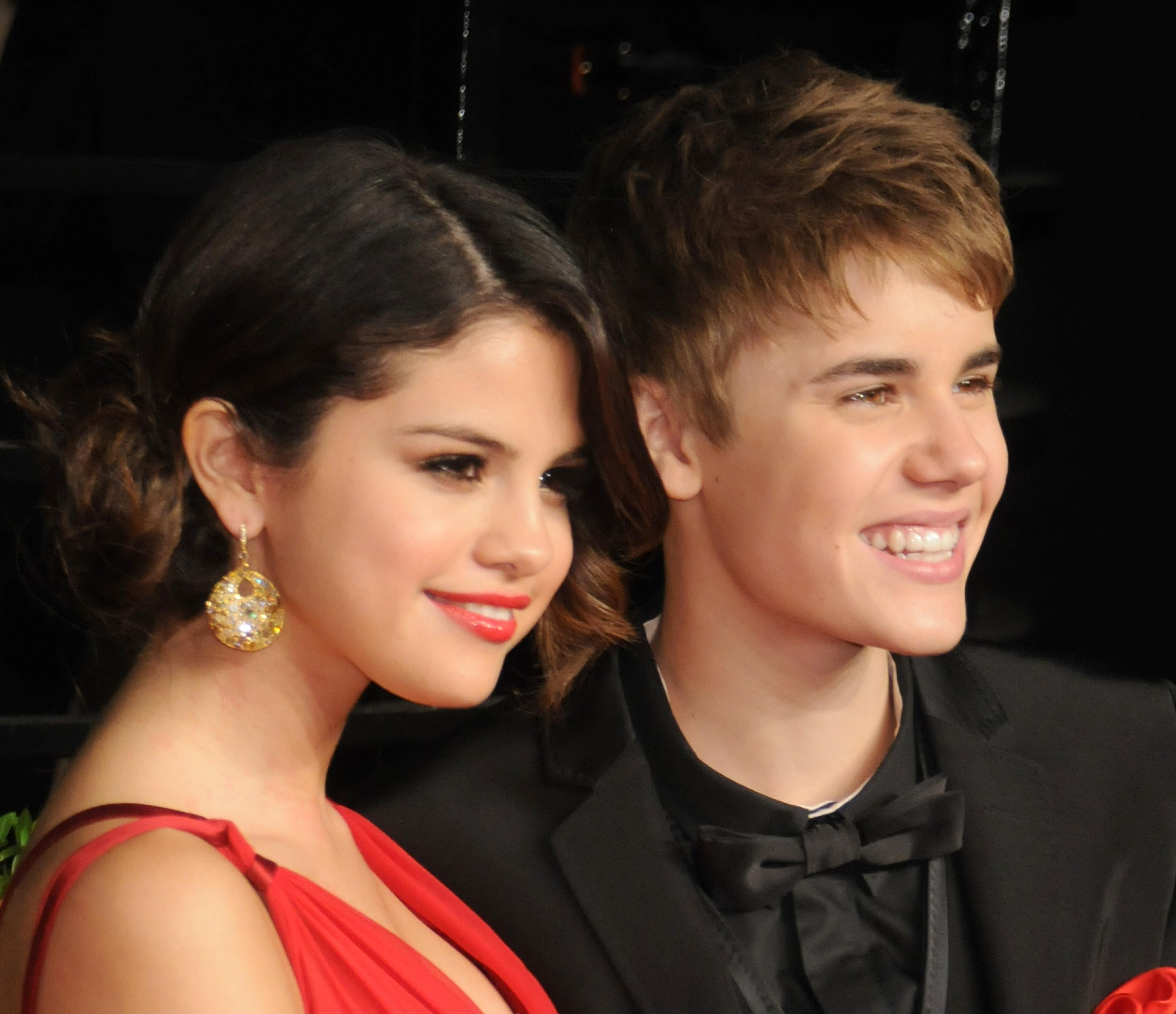 Selena Gomez wears a plunging red dress and Justin Bieber wears a black tux at the 2011 Vanity Fair Oscar party.