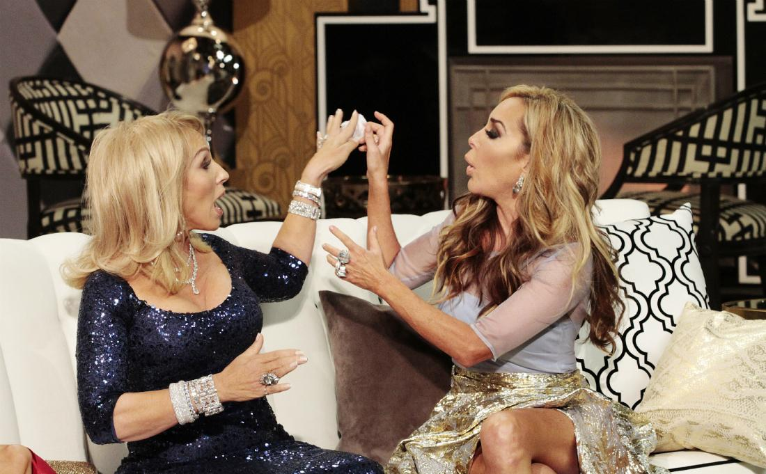 Lea Black in a glittery dress sits on a sofa during a confrontation with Marysol Patton who wears a flowery dress and has her arms raised.