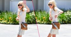Anna Faris wears a white top and skirt while walking towards her car.