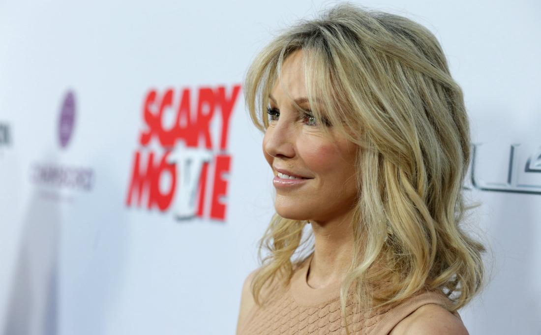 Heather Locklear, in a golden dress, stands on the red carpet and smiles.