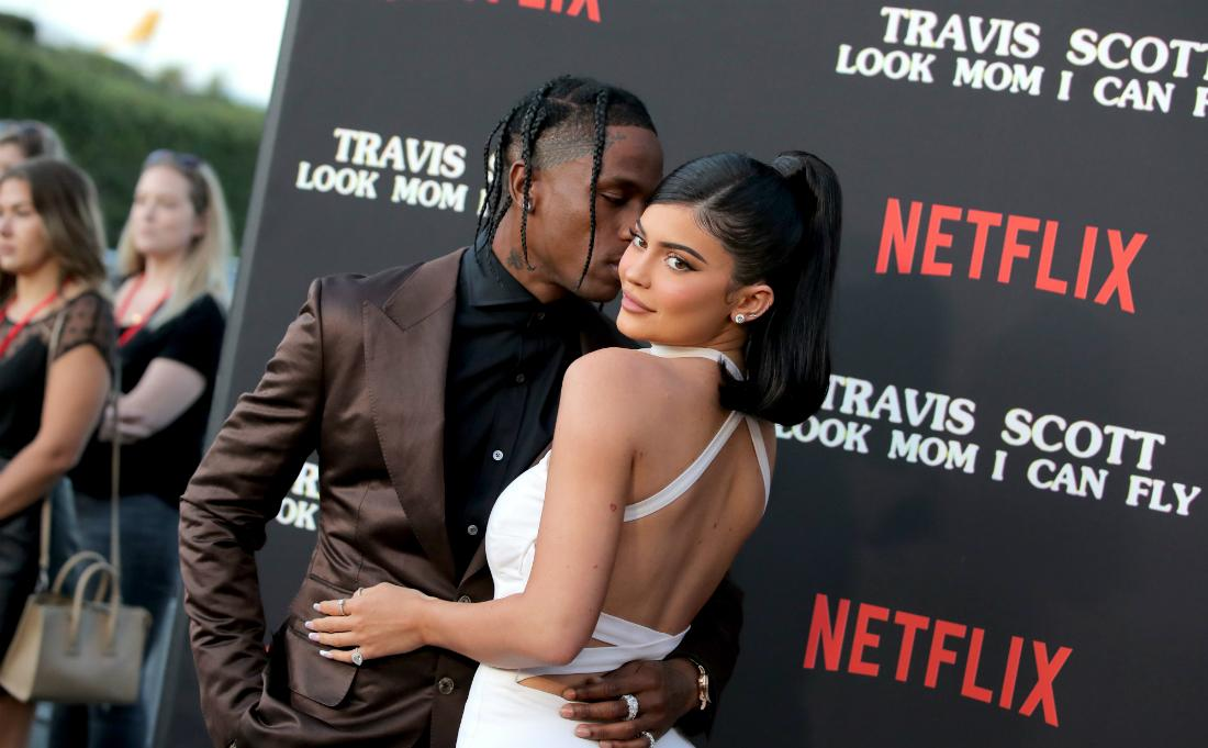 Travis Scott, in a brown jacket and black shirt, kisses Kylie Jenner, who wears a white dress, on the red carpet.