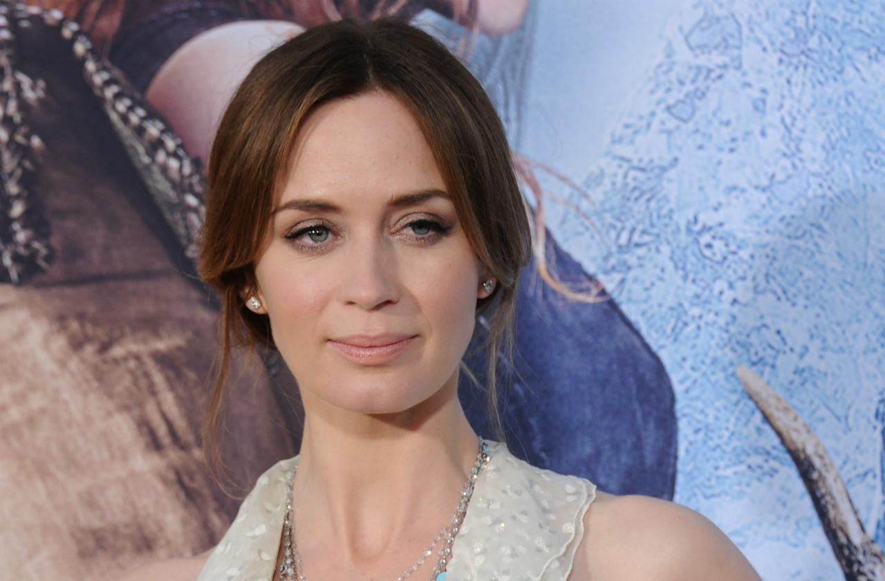Emily Blunt wears a sleeveless flowing v-neck dress and hair in an updo at The Huntsman Winter's War premiere in 2016.