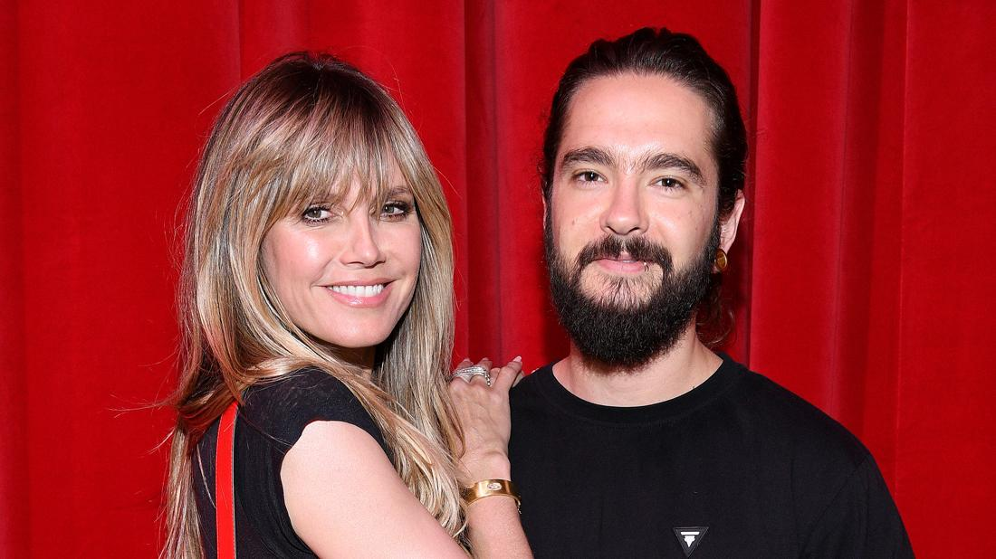 Heidi Klum Tom Kaulitz Smiling And Embracing In Front Of A Red Curtain