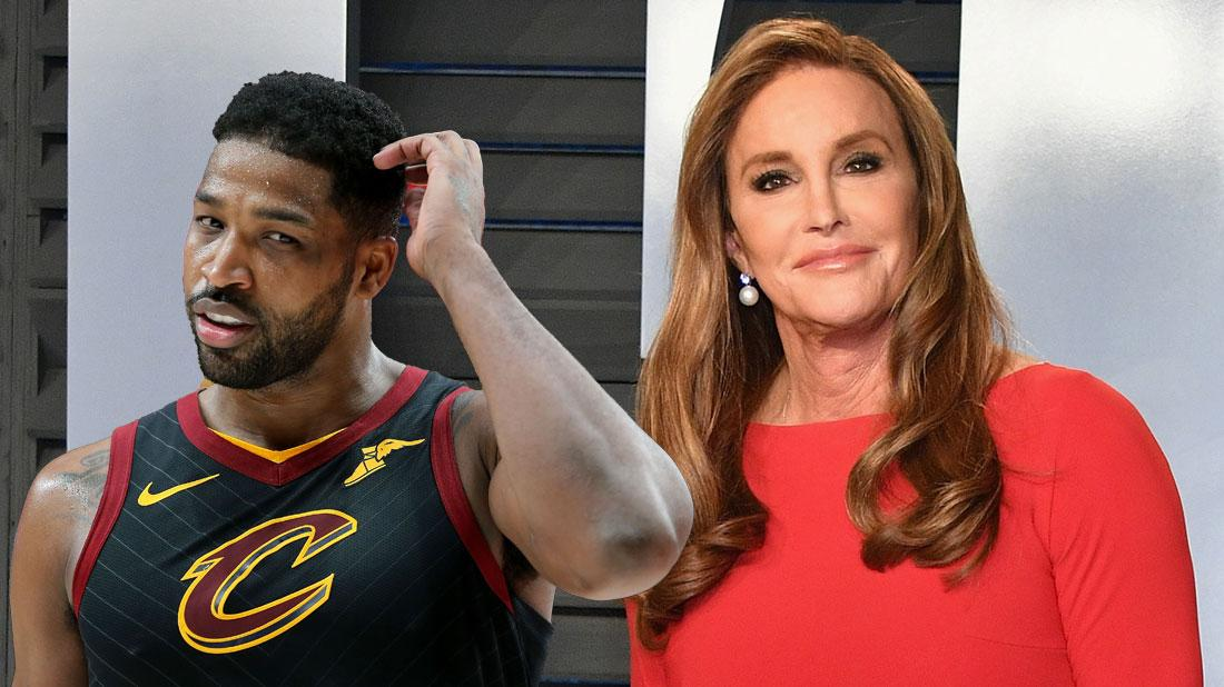 Caitlyn Jenner wears a red dress. Tristan Thompson wears his Cleveland Cavaliers jersey.