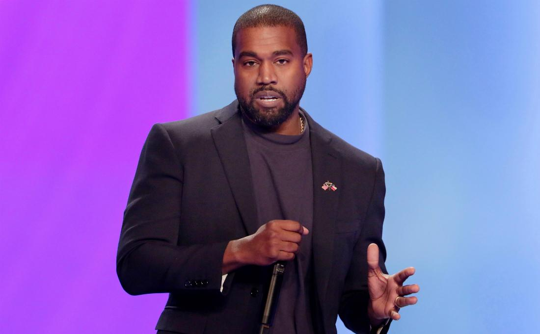 Kanye West, on stage and holding a mic, wears a dark jacket over a dark top.