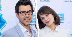 Jacob Pechenik Wearing Glasses, Blue Shirt And Suit With Zooey Deschanel Wearing White Blouse Standing In Front Of SAVE THE BAY Step And Repeat
