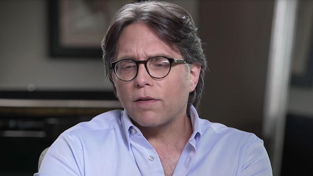 Keith Raniere of NXIVM in Glasses and Blue-Purple Shirt Eyes Looking Down