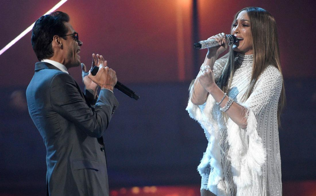 Marc Anthony, in a blue suit, sings with Jennifer Lopez who wears a white dress.