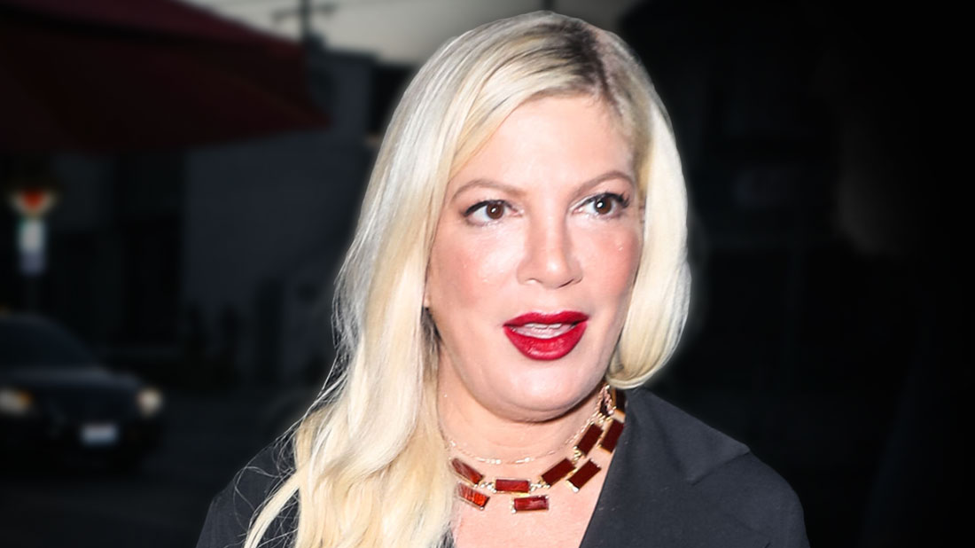 Tori Spelling Wearing Red Lipstick, Black Shirtdress With Brownish Red Necklace