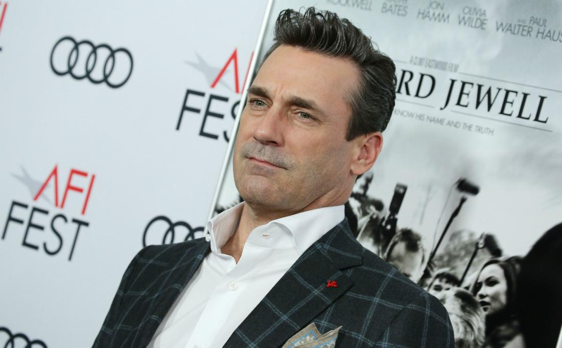 Jon Hamm, in a white shirt and check jacket, stands on the red carpet.