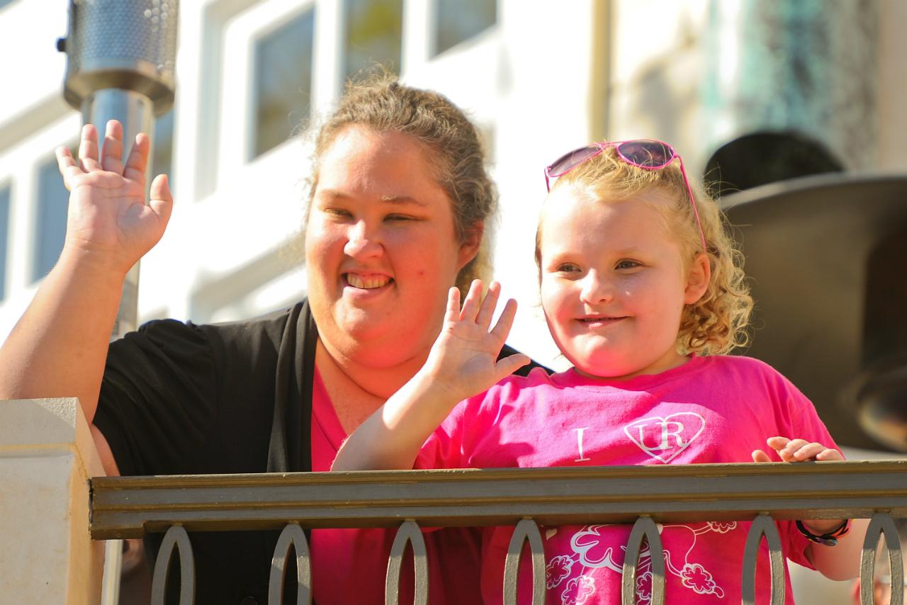Honey Boo Boo Alana Thompson and Mama June wave at The Grove in this 2012 image, with Alan wearing a pink t-shirt and her mom wearing a black cardigan.