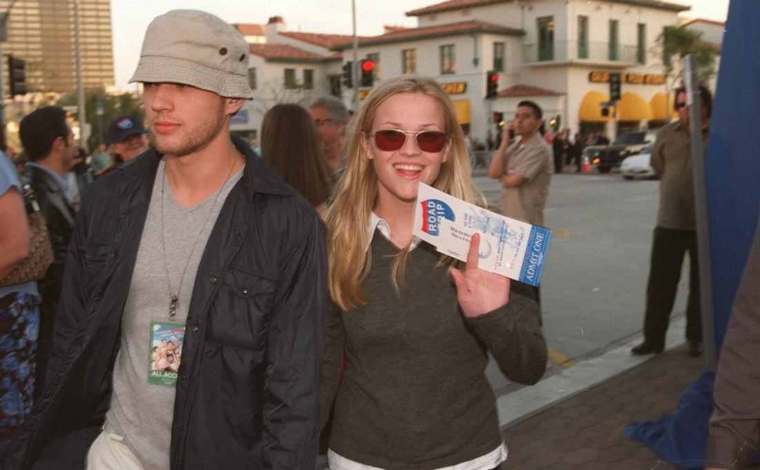 Ryan Phillippe, in a grey tshirt, hat, and black coat, walks alongside Reese Witherspoon who wears a grey sweater over a white shirt.