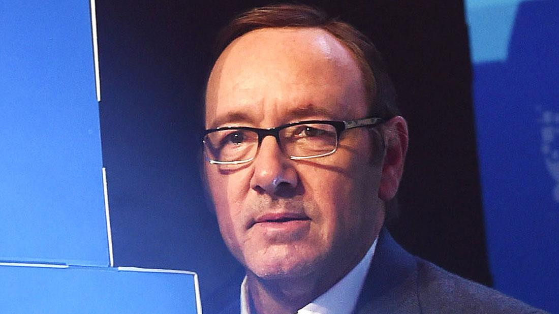 Kevin Spacey With Glasses, White Shirt and Grey Jacket With Blue Background